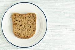 Tranche de pain de grain avec le moule D'un plat blanc avec une rayure bleue Sur une table en bois image stock