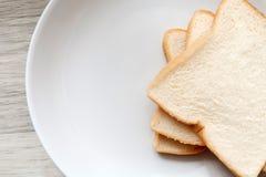Tranche de pain grillée du plat blanc Photos stock
