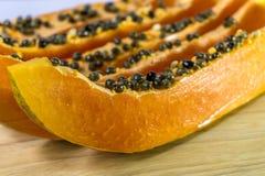 Tranche de papaye avec des graines sur le fond en bois Images stock