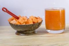 Tranche de papaye avec du jus d'isolement sur la table en bois Photos stock