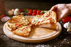 Tranche de pizza à disposition au-dessus de la table avec la pizza Photos stock
