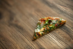 Tranche de pizza dans une planche en bois images libres de droits