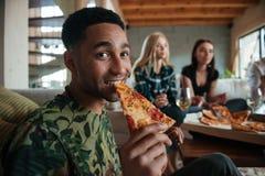 Tranche de pizza mangeuse d'hommes tout en traînant avec des amis Photographie stock libre de droits