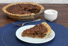 Tranche de tarte aux noix de pécan avec le tarte entier à l'arrière-plan Images stock
