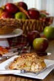 Tranche de tarte aux pommes avec le panier des pommes Images stock