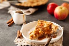 Tranche de tarte aux pommes fraîchement cuite au four avec de la sauce et la cannelle à caramel images stock