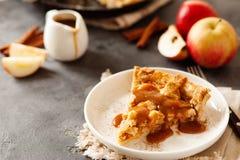 Tranche de tarte aux pommes fraîchement cuite au four avec de la sauce et la cannelle à caramel photos libres de droits