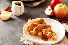 Tranche de tarte aux pommes fraîchement cuite au four avec de la sauce et la cannelle à caramel image stock