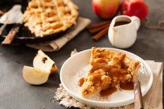 Tranche de tarte aux pommes fraîchement cuite au four avec de la sauce et la cannelle à caramel photographie stock