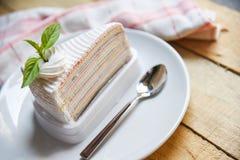 Tranche et cuillère de gâteau de crêpe du plat blanc sur le fond en bois de table photos stock