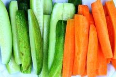 Tranche fraîche de concombre et de carottes d'isolement sur le fond blanc photos stock