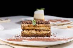 Tranche gastronome de gâteau de chocolat du plat blanc Photographie stock libre de droits