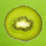 Tranche gentille de kiwi, couverte de bulles sur le vert Photographie stock libre de droits