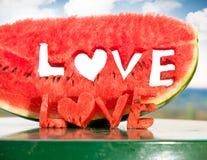 Tranche juteuse fraîche de pastèque avec le mot de lettres d'amour Image stock