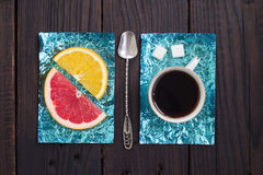 Tranche orange et une tasse de café sur des supports faits en aluminium coloré Photo libre de droits