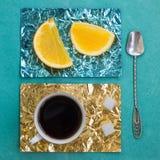 Tranche orange et une tasse de café sur des supports faits en aluminium coloré Photos stock