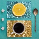 Tranche orange et une tasse de café sur des supports faits en aluminium coloré Photographie stock libre de droits
