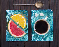Tranche orange et une tasse de café sur des supports faits en aluminium coloré Images stock