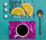 Tranche orange et une tasse de café sur des supports faits en aluminium coloré Images libres de droits