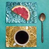 Tranche orange et une tasse de café sur des supports faits en aluminium coloré Image libre de droits