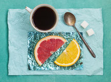 Tranche orange et une tasse de café sur des supports faits en aluminium coloré Image stock