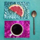 Tranche orange et une tasse de café sur des supports faits en aluminium coloré Photo stock