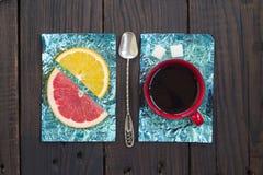 Tranche orange et une tasse de café sur des supports faits en aluminium coloré Photographie stock
