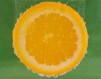Tranche orange submergée avec des bulles images stock