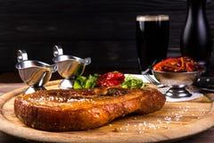Tranche rôtie de jambe de porc avec l'os Deux sauces, haricots rouges, oignon, paprika sur le fond en bois et verre noir de Photo stock