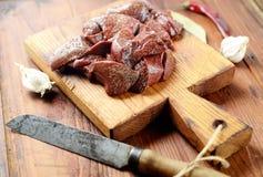 Tranches crues de foie sur une planche à découper, un ail, un poivre et une feuille de laurier, couteau sur un fond en bois image stock