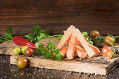 Tranches crues de patate douce avec des pepers piments, tomates et verdure sur un fond foncé de conseil en bois photo stock