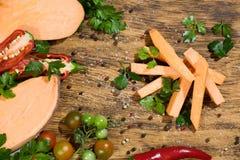 Tranches crues de patate douce avec des pepers piments, tomates et verdure sur un fond foncé de conseil en bois images libres de droits