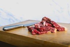 Tranches crues fraîches de bifteck de viande de boeuf sur le conseil coupé en bois au-dessus du fond blanc image stock