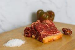 Tranches crues fraîches de bifteck de viande de boeuf sur le conseil coupé en bois au-dessus du fond blanc photo stock