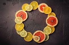 Tranches d'agrumes de citron, orange, pamplemousse dans la forme de cercle sur le fond foncé Photo libre de droits