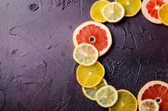 Tranches d'agrumes de citron, orange, pamplemousse dans la forme de cercle sur le fond foncé Images libres de droits