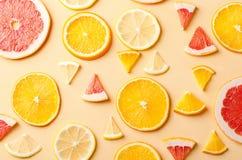 Tranches d'agrumes de citron, orange, pamplemousse sur le fond jaune Photographie stock