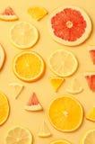 Tranches d'agrumes de citron, orange, pamplemousse sur le fond jaune Image libre de droits