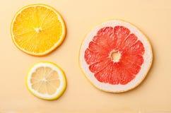 Tranches d'agrumes de citron, orange, pamplemousse sur le fond jaune Image stock