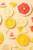 Tranches d'agrumes de citron, orange, pamplemousse sur le fond jaune Photos stock