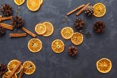 Tranches d'orange, de bâtons de cannelle et de cônes secs de pin sur le DA photo stock