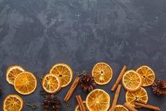 Tranches d'orange, de bâtons de cannelle et de cônes secs de pin sur le DA photo libre de droits