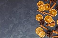 Tranches d'orange, de bâtons de cannelle et de cônes secs de pin sur le DA image libre de droits