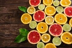 Tranches d'oranges, de chaux, de pamplemousses et de citrons Au-dessus de la table en bois Photographie stock