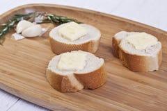 Tranches de baguette avec du beurre Photos stock
