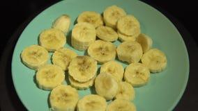 Tranches de banane d'un plat azuré tourner sur un fond noir banque de vidéos