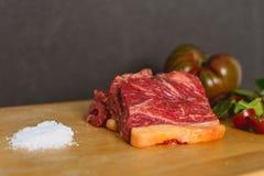 Tranches de bifteck de boeuf cru frais sur le conseil en bois sur le fond noir avec de la salade et des tomates images libres de droits
