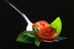 Tranches de cerise de tomate et basilic vert Image libre de droits