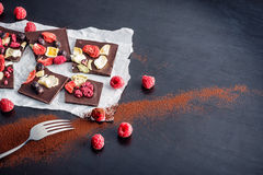 Tranches de chocolat sucré avec des fruits sur le livre blanc avec le fruit du plat, dessert doux sur le fond noir image pour la  Photos stock