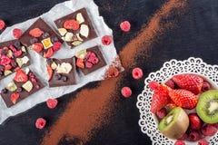Tranches de chocolat sucré avec des fruits sur le livre blanc avec le fruit du plat, dessert doux sur le backgroud noir image pou Photo stock
